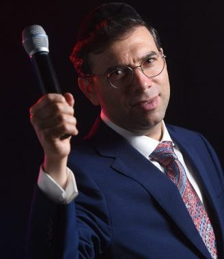 Photo of Michoel Pruzansky with a microphone, blue suite and multi colored tie
